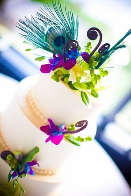 a wedding cake topped with purple blue and green blooms and peacock feathers