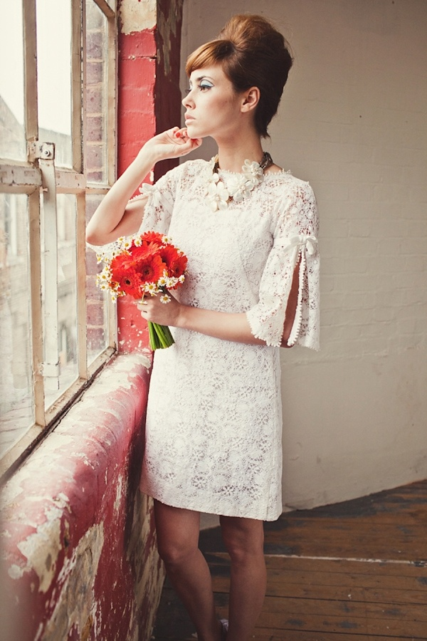 a short lace hippie inspired wedding dress with bell sleeves with cuts and a high neckline is very cool and bold