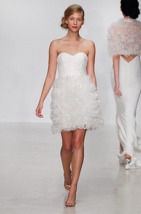 a strapless wedding dress with a plain draped bodice and a floral over the knee skirt for a modern girlish look
