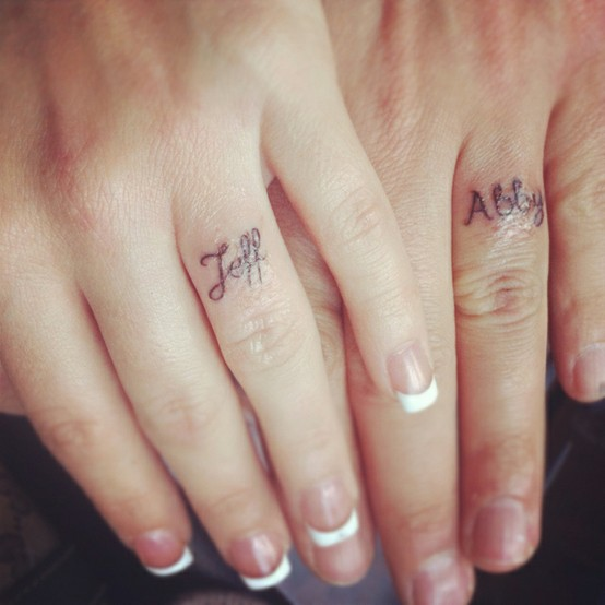 Partner names tattooed in cursive is a classic idea for wedding rings