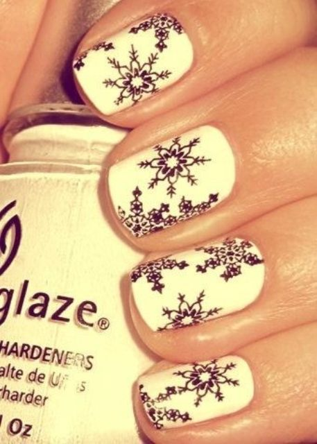a white manicure with black snowflake stickers is a stylish and contrasting idea to make your look extra bold