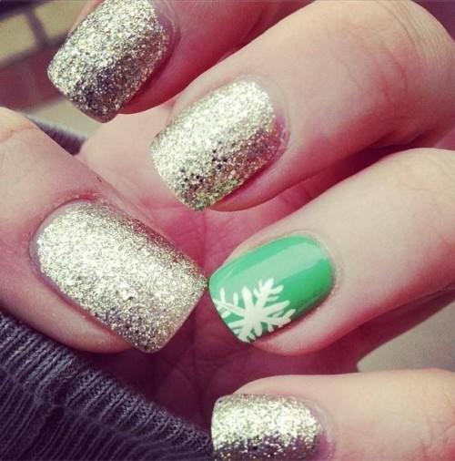 a gold glitter manicure and a bold green accent nail with a snowflake for a modern color-loving bride