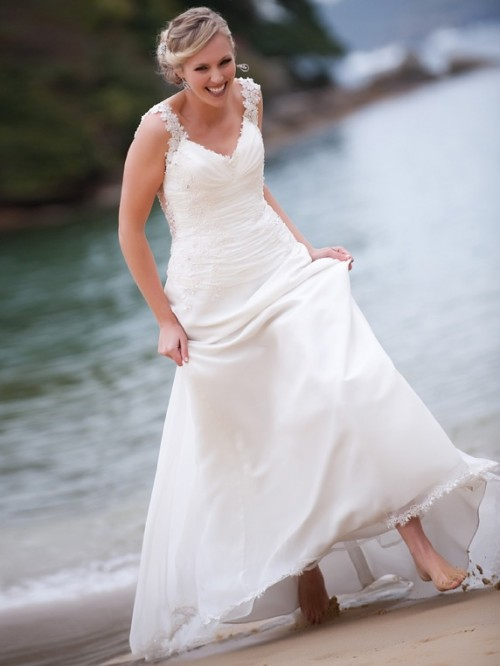 an A-line wedding dress with lace straps, a draped bodice and a V-neckline will fit a more formal wedding at the beach
