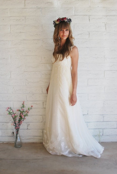 a lace A-line wedding dress with straps and a train and a floral crown to look super romantic