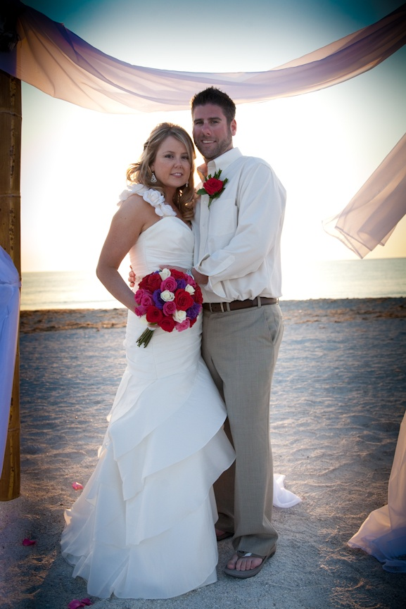 a draped fitting wedding dress with floral straps and an asymmetrical skirt for a romantic and more formal look