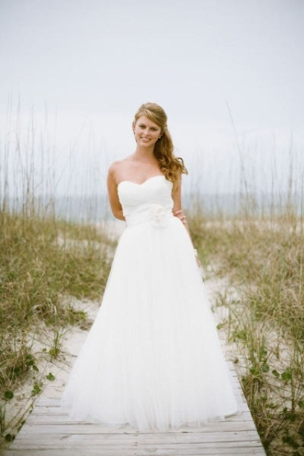 a strapless A-line wedding dress with a sash and a fabric flower is a beautiful and romantic formal wedding gown
