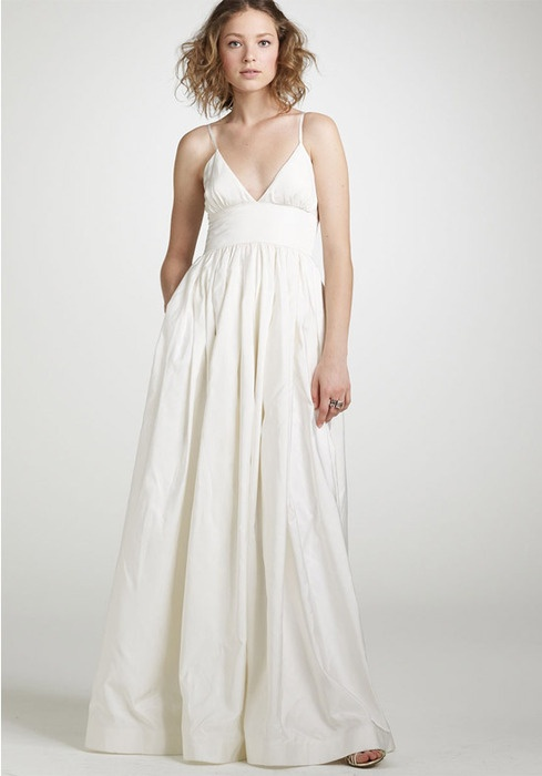 a simple and casual A-line plain wedding gown with a V-neckline and spaghetti straps for a casual beach wedding