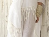 a gypsy-style flowy wedding gown with wide sleeves and tassels and multiple bracelets for a flowy beach look