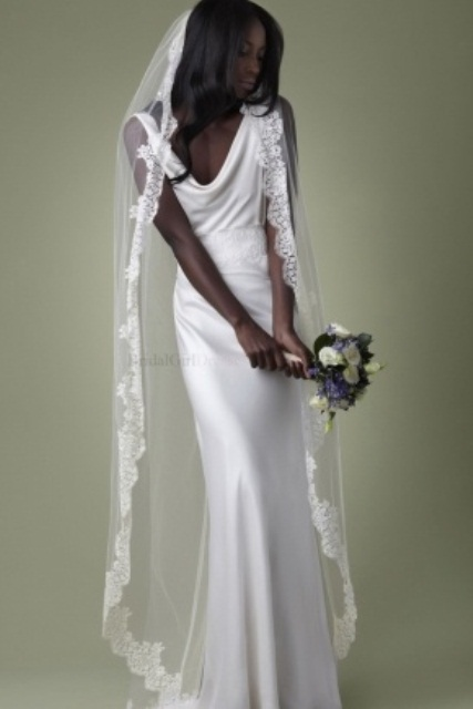 a minimalist silk sheath wedding dress and a long veil with a lace trim for a modern beach bride