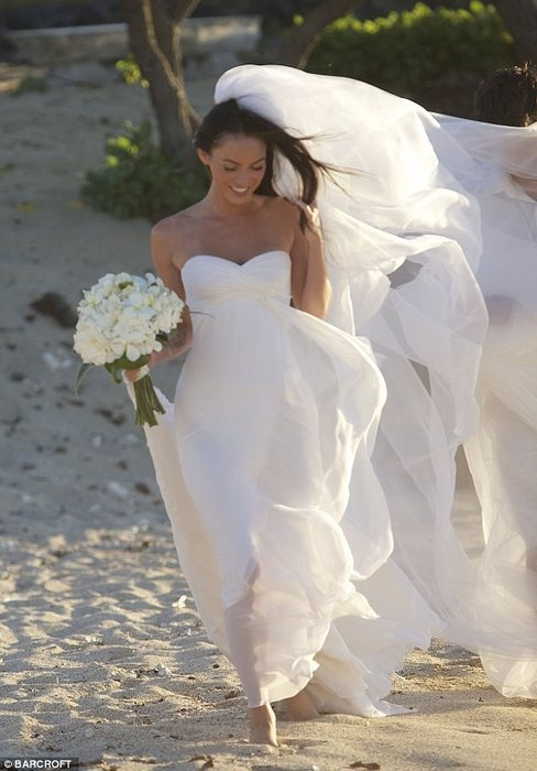 Meghan Fox wearing a flowy strapless wedding gown with a draped bodice and a long veil that flies