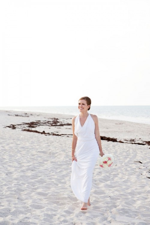 a modern white draped sheath wedding dress and bare feet for an elegant and stylish bridal look