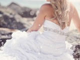 a classic strapless sheath wedding dress with a ruffle skirt and an embellished sash