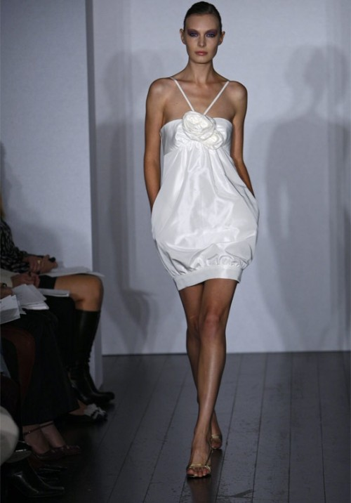 a modern short wedding dress with paghetti sraps and a fabric flower plus pockets for amodern beach bride