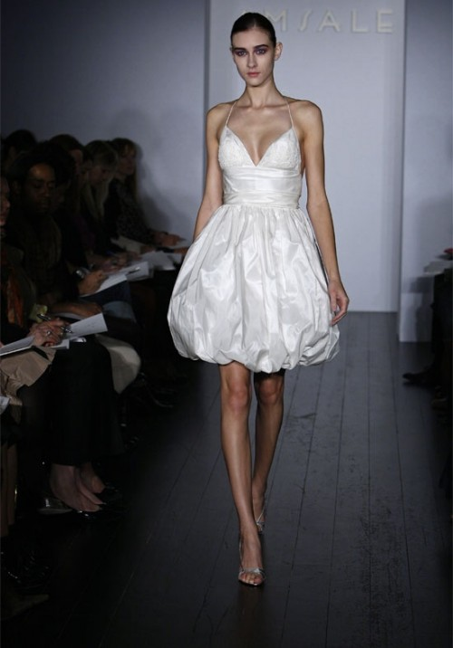 a whimsy short wedding dress of a shiny fabric, with spaghetti straps and a draped skirt