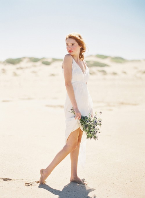 a simple modern plain short wedding dress with a deep neckline and spaghetti straps for a modern beach bride