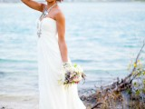 a strapless and draped maxi wedding gown with a train, layered necklaces and bracelets for a chic beach bridal look