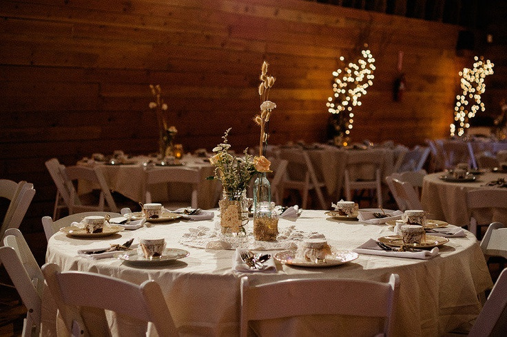 a neutral barn wedding tablescape with neutral linens, a dried bloom centerpieces and vintage porcelain and mugs