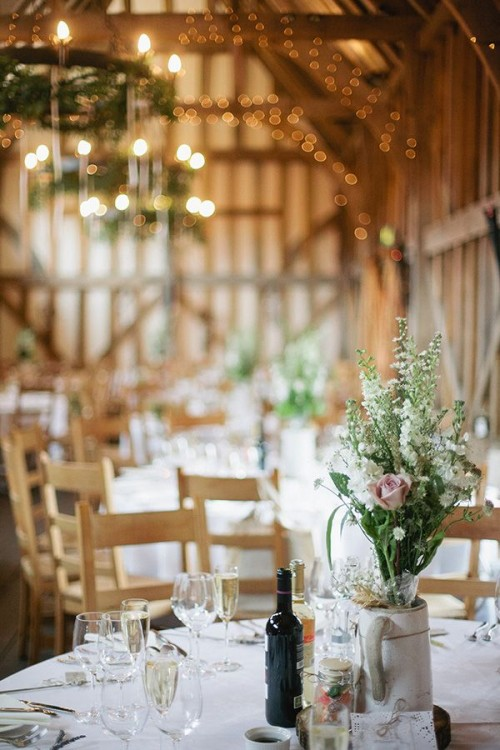 a chic neutral barn wedding tablescape with white linens, a neutral bloom wedding centerpiece in a vintage jug and simple cutlery