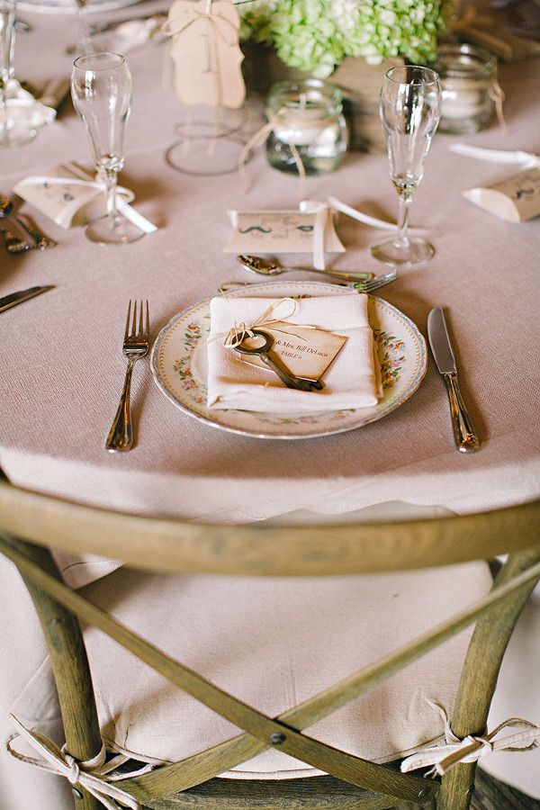 a neutral barn wedding table with simple linens, green hydrangeas, elegant cutlery and glasses
