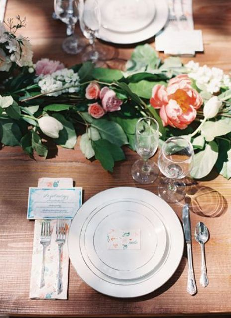 a chic and fresh wedding barn tablescape with an uncovered table, a greenery and pink bloom runner, bright stationery