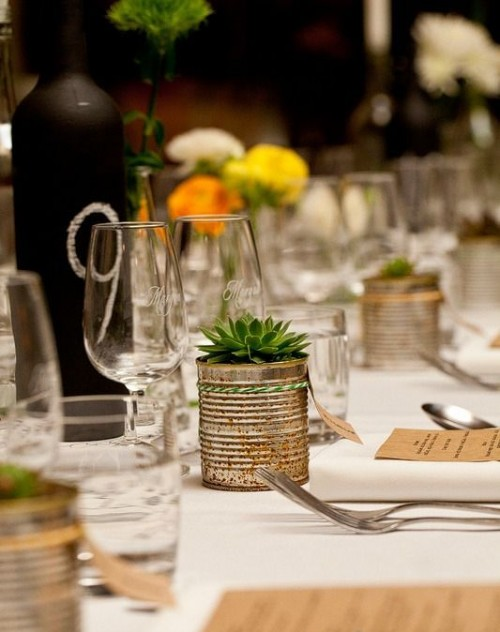 a simple barn wedding tablescape with white linens, tin cans with succulents and bright blooms, a chalkboard wine bottle with a table number