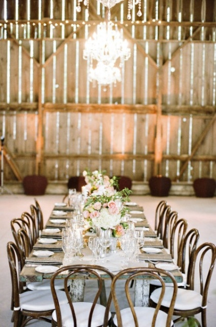 a barn wedding tablescape with an uncovered table, a white table runner, white and pink blooms and greenery for a refined touch