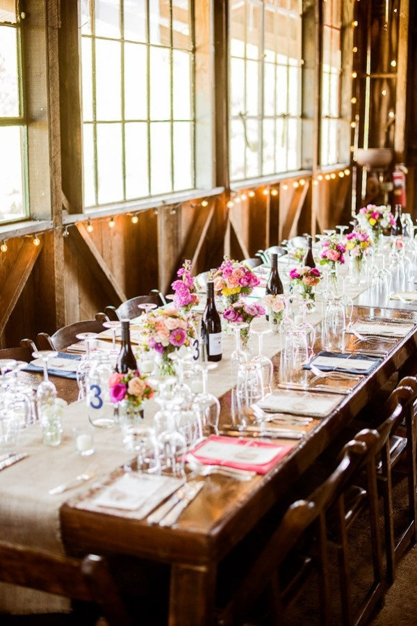a bright barn wedding tablescape with a burlap table runner, colorful blooms and greenery, colorful napkins for a summer wedding