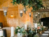 a barn wedding table setting with a grey tablecloth, greenery, white and peachy blooms, candles and an overhead greenery installation with candles