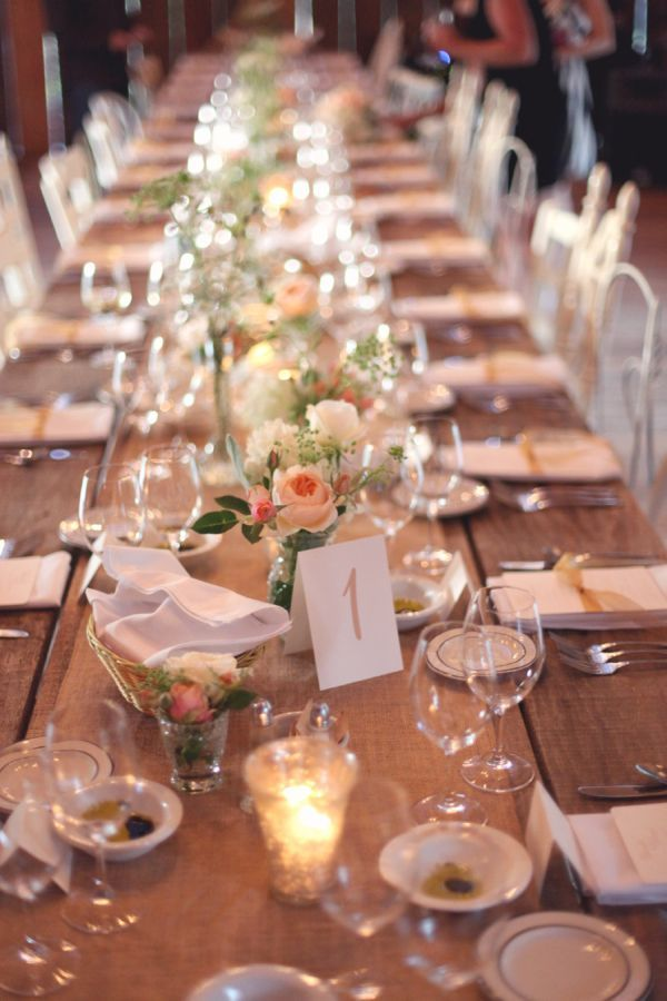 a romantic barn wedding table setting with an uncovered table, a burlap table runner, peachy and white blooms, white linens