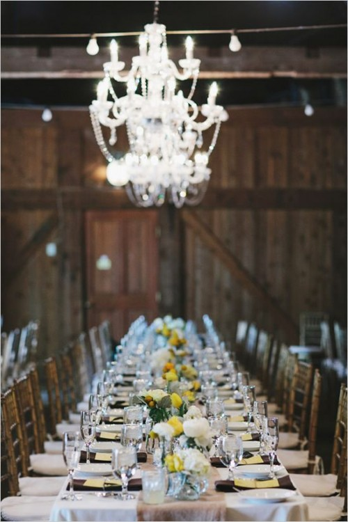 a vintage barn wedding tablescape with brown napkins, white and yellow blooms and greenery and all-neutral everything