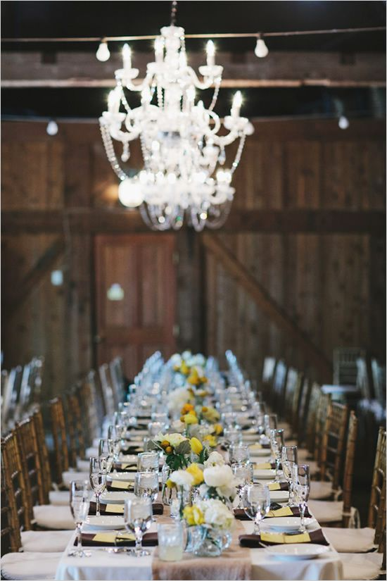 a vintage barn wedding tablescape with brown napkins, white and yellow blooms and greenery and all neutral everything