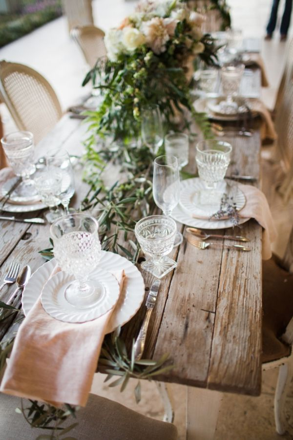 a simple barn wedding table setting with an uncovered table, greenery and a greenery and white bloom centerpiece and white linens