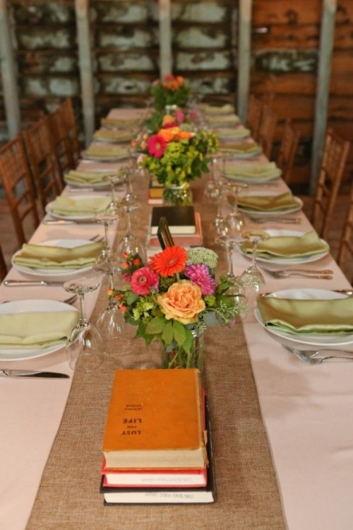 a bright rustic wedding tablescape with a burlap table runner, bright blooms and greenery, vintage books and colorful napkins