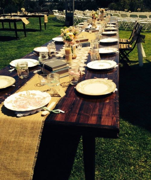 a barn wedding tablescape with an uncovered table, a burlap table runner, vintage books, a neutral centerpiece and floral plates