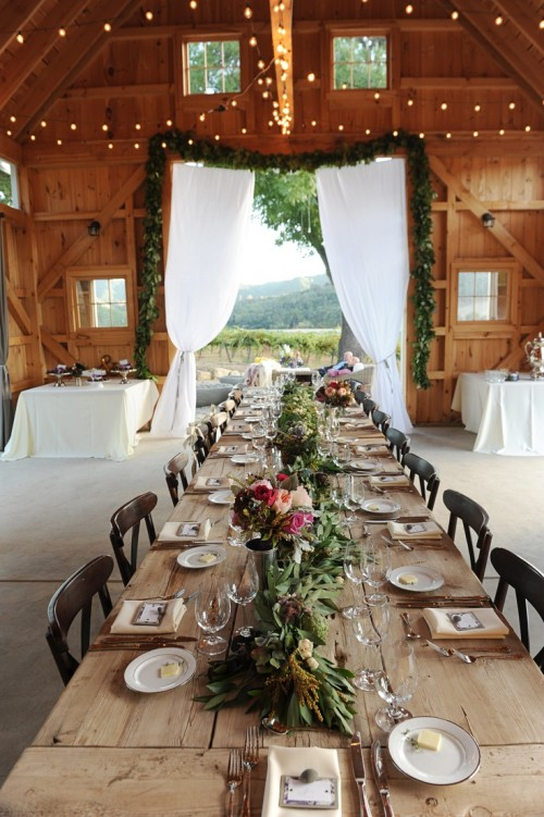a barn wedding table setting with an uncovered table, a greenery table runner, bright blooms and neutral linens