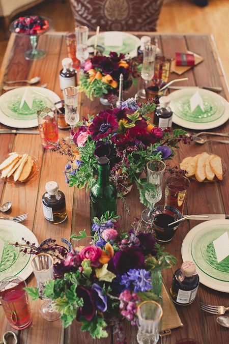 a colorful barn wedding tablescape with an uncovered table, colorful blooms, bright napkins, plates and glasses