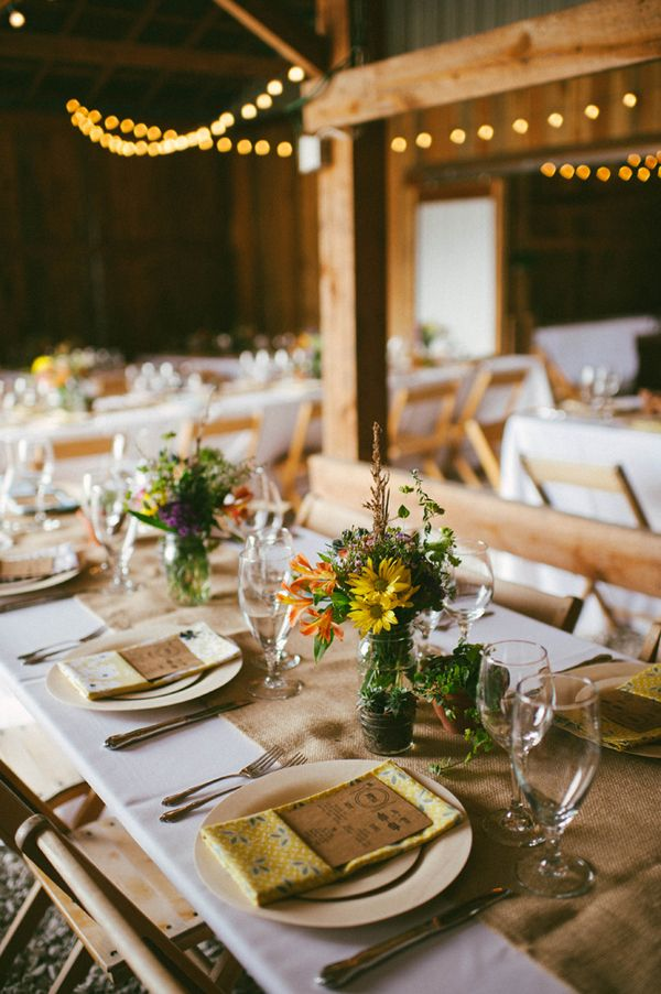 a barn wedding tablescape with a burlap table runner, a colorful floral centerpiece, colorful printed napkins