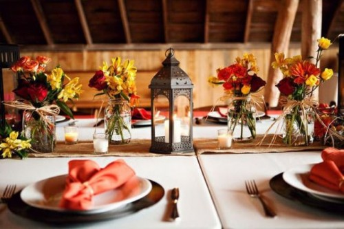 a colorful vintage barn wedding tablescape with bright floral centerpieces, a candle lantern, a burlap table runner and bright napkins