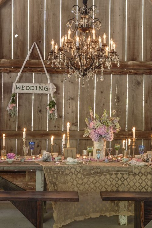 a vintage pastel barn wedding table with pastel florals, colored glasses, candles and votives and a lace table runner