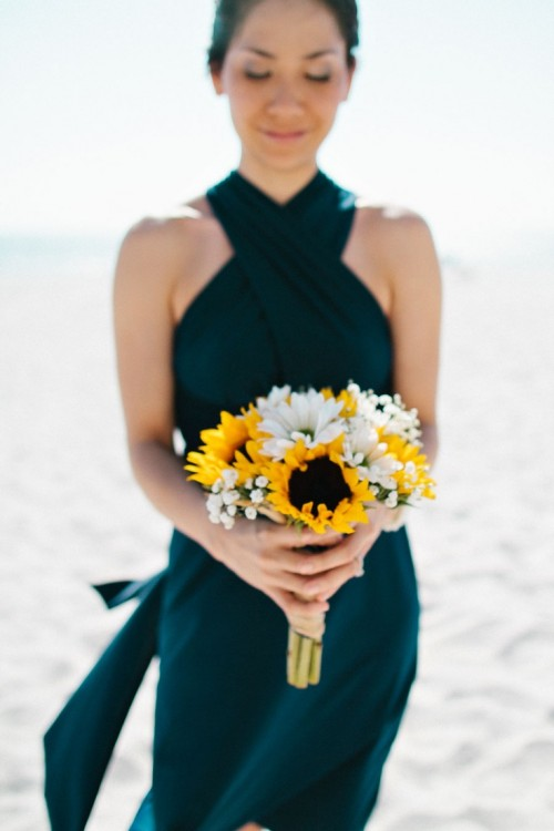 an elegant black bridesmaid dress with a criss cross neckline is a stunning idea for a refined beach wedding
