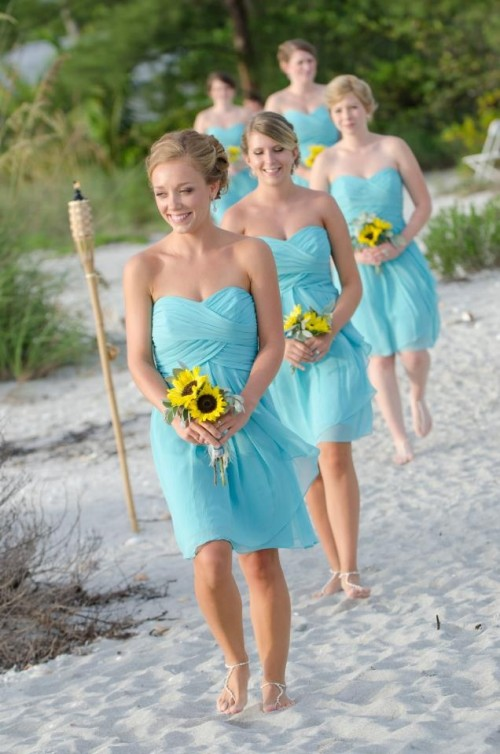turquoise strapless mini dresses with draped bodices are a bright touch at the wedding on the beach