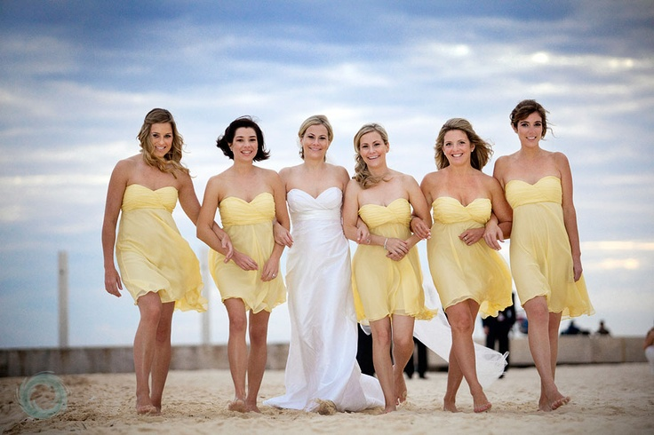 yellow strapless short dresses with draped bodices are a bright touch to a beach wedding