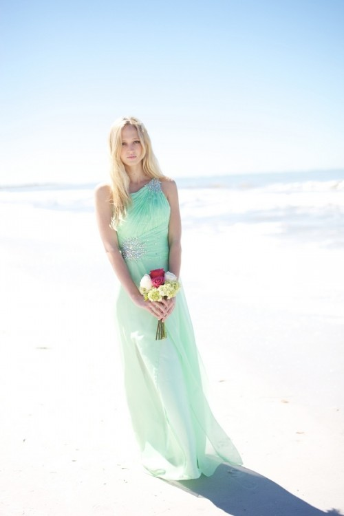 a light green maxi bridesmaid dress with embellishments on the shoulder and waist for a pastel beach wedding