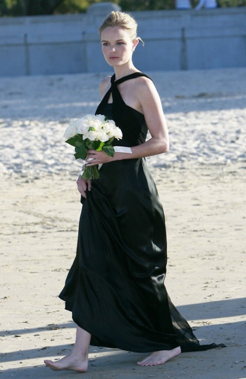 a black silk maxi dress with a train and a halter neckline is a refined and stylish piece for a modern beach wedding