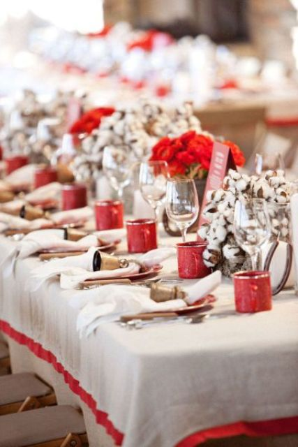 a cozy and fun Christmas tablescape with red bloom and cotton centerpieces, red signs and large bells for a bold look