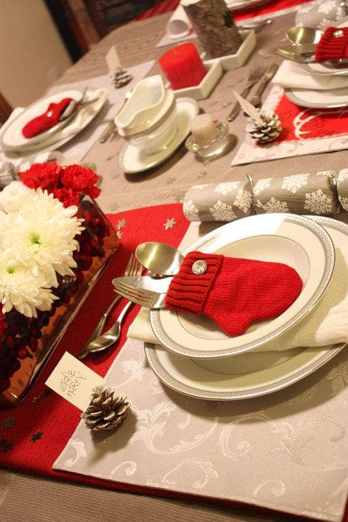 a cozy neutral and red Christmas tablescape with printed placemats and runners, a red and white bloom centerpiece, a snowflake napkin and a red mitted cutlery pocket