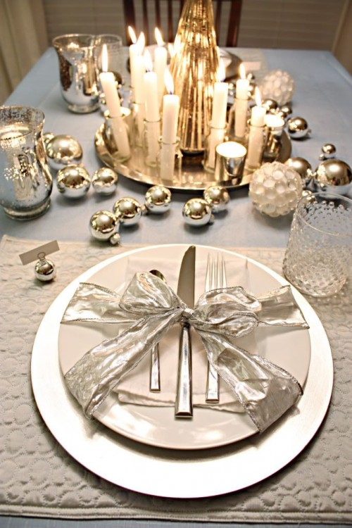 a bright metallic Christmas tablescape with metallic ornaments, mercury glass candleholders, a bottle and candles centerpiece and a silver ribbon bow