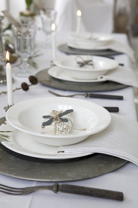 a natural and vintage-inspired tablescape with rough metal cutlery and chargers, white tall adn thin candles, branches and pinecones feels Nordic