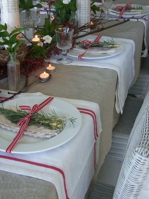 a neutral rustic Christmas tablescape with a burlap tablecloth, striped placemats, a greenery and branch runner, candles, evergreens and red and white ribbons