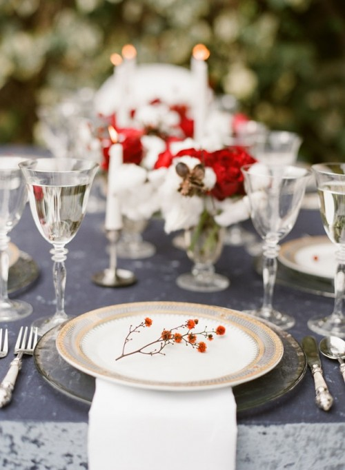 a chic grey and red Christmas tablescape with red and white blooms, marble chargers, berries and sivler cutlery and silver glasses